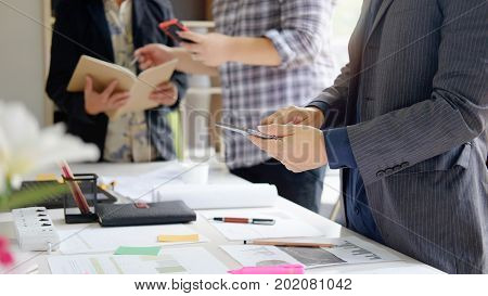 Business man talking to meeting making business decision in office with paper report on office desk.