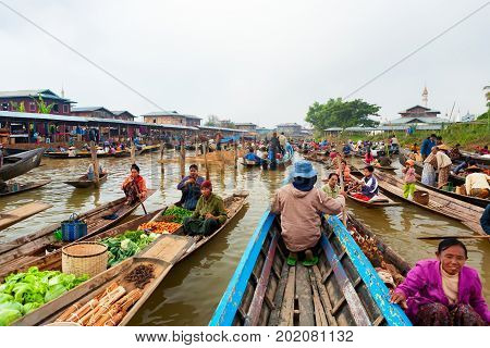 Inle Lake Myanmar - January 04 2007: Burmese native people sell vegetables fruits and craft on traditional floating morning market at stilt houses village near Nyaungshwe Township on Inle lake.
