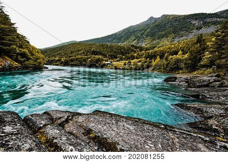 Beautiful turquoise whitewater river and nature in the mountains of Norway surrounded by green trees and forest