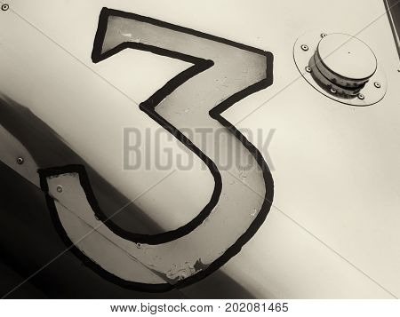 the number three painted on a vintage silver racing car with shiny copper fuel tank cover and rivets