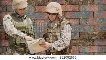 Digital composite of Soldier men looking at a map against a brick wall