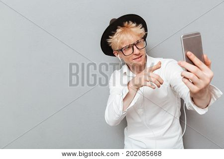 Picture of handsome caucasian man wearing glasses standing isolated over grey wall near copyspace. Looking aside and listening music with earphones while make selfie.