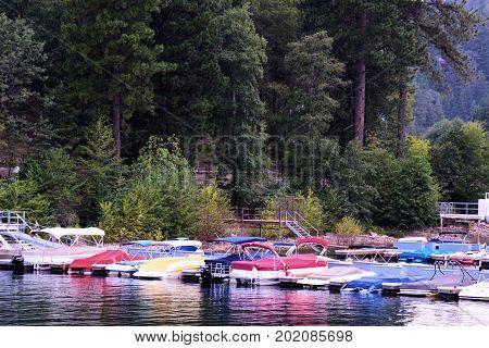 August 29, 2017 in Lake Arrowhead, CA:  Yachts and boats at a dock surrounded by a pine forest taken at the Lake Arrowhead Marina where people can ride their yachts and tourists can ride rental boats on the lake taken in Lake Arrowhead, CA