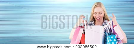 Digital composite of Shopper looking into bags against blurry blue background