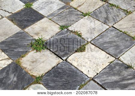 Horizontal image of checkerboard background of light and dark gray stone squares.