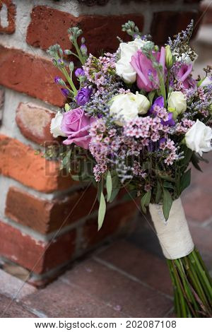 Beautiful wedding bouquet leaning against a brick wall