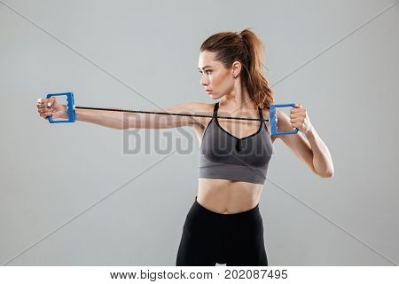 Side view of a sports woman doing exercises with hand expander over gray background