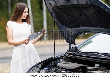 attractive woman in front of her car broken car with user guide