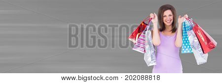 Digital composite of Shopper holding up bags against blurry grey background