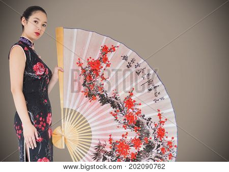 Digital composite of Geisha and giant fan against brown background