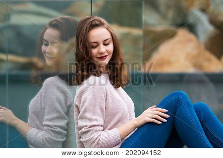 Reflection of beautiful cute fashionable girl in modern glass building, girl dreaming