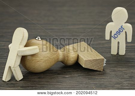 Wooden figure is mobbed and was stamped as loser