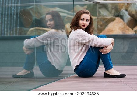 Reflection of beautiful cute fashionable girl in modern glass building