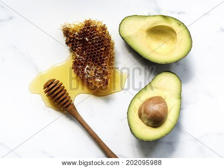 Aerial view of fresh avocado and honey on white marble background