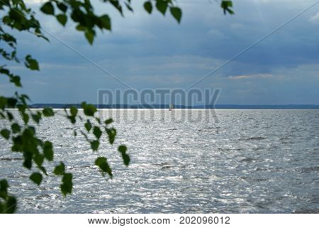 One-masted sailboat with a straight sail in the distance under a stormy sky