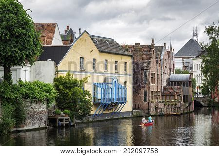 GHENT BELGIUM - JUNE 22 2016: Wide picture of a canal in a cloudy day with a red boat houses trees flowers and a small bridge in Ghent.