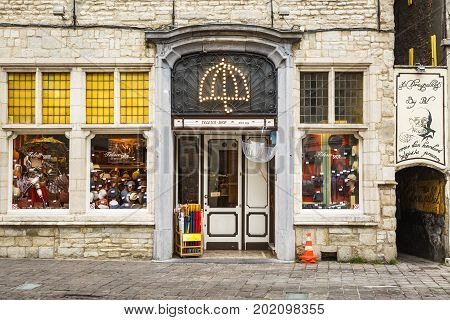 GHENT BELGIUM - JUNE 22 2016: Horizontal picture of an umbrella and hat store with a luminous umbrella shaped sign on the entrance with an alley in the right side. Downtown Ghent.