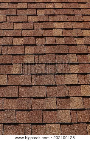 Texture of grey and brown roof tiles on a bright day