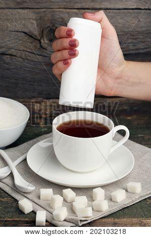 Female Hand Throwing Sweetener Tablets In Cup Of Tea
