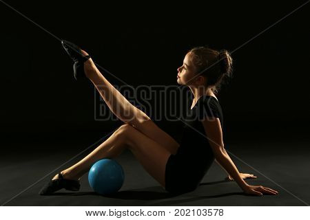 Young Girl Gymnast With Ball On Black Background
