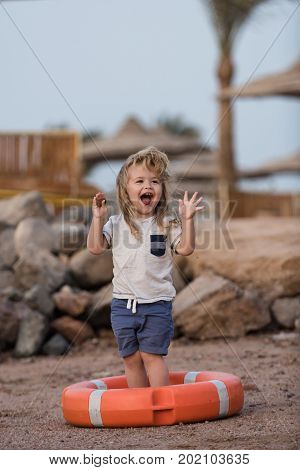 Small kid laughing in orange life ring at beach. Boy child standing with hands up in life buoy. Happiness and expressive emotions. Baby care and childhood concept. Safety on water on summer vacations.