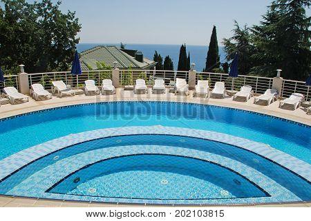 CRIMEA, UKRAINE - JULY 21, 2009: Beautiful landscape with white outdoor sun beds and swimming pool on summer sea resort, Crimea, Ukraine