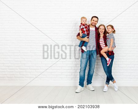 Happy family mother father son daughter on a white blank brick wall background