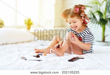 Happy funny child little girl with hair curlers does a pedicure paints nails and laughs