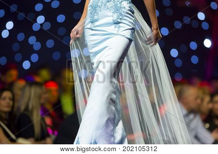 Sofia, Bulgaria - 23 March, 2017: A female model walks the runway in beautiful blue dress during a Fashion Show. Fashion catwalk event showing new collection of clothes.