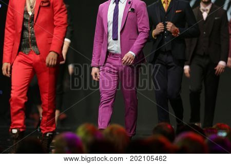 Sofia, Bulgaria - 23 March, 2017: Male models walk the runway in beautiful red and pink suits during a Fashion Show. Fashion catwalk event showing new collection of clothes.