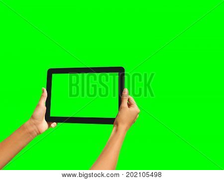 Young girl hand holding a tablet on green screen