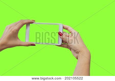 Young girl hand holding mobile smart phone on green screen