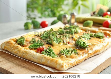 Traditional quiche with broccoli and cheese on wooden board