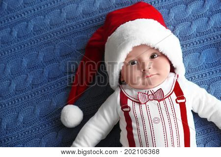 Cute little baby in Santa hat on knitted fabric