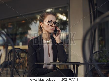 Serious business woman in elegant suit and glasses talking on the cellphone sitting in the outdoor cafe. Bad news.
