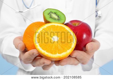 Young female nutritionist with fresh fruits, closeup. Weight loss concept