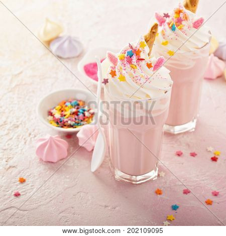 Pink unicorn milkshakes with whipped cream, sugar and sprinkles poster