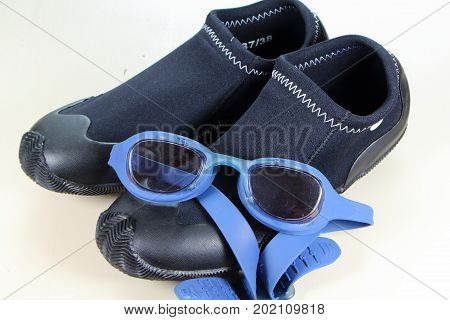 Blue swimming goggles above black swimming boot