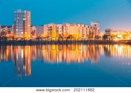 Night View Of Urban Residential Area Overlooks To City Lake Or River And Park In Evening Illumination, Reflecting In Water Surface. Spring In Gomel, Belarus. City Residential Architecture