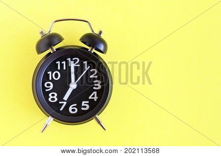 Alarm clock with six o'clock on yellow background in minimalistic retro pop art style with place for text. Wake up concept. Back to school. Copy space. Top view.