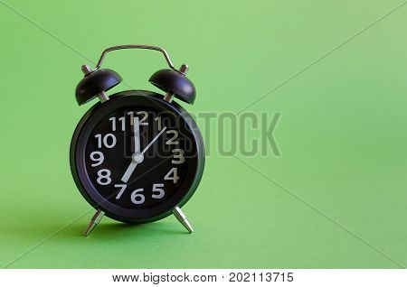 Alarm clock with seven o'clock on green background in minimalistic retro pop art style with place for text. Wake up concept. Back to school. Copy space.