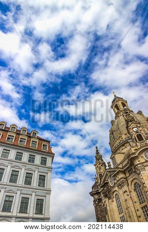 Famous Church Frauenkirche in Dresden against a beautiful blue sky with white clouds. Fragment. Saxony, Germany