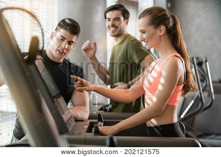 Motivated young woman increasing the speed of the treadmill during a workout session supervised by a professional personal trainer