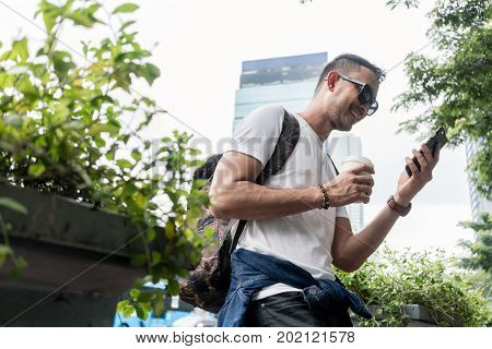 Low angle view portrait of a young man smiling while using a mobile phone outdoors during summer vacations in Asia