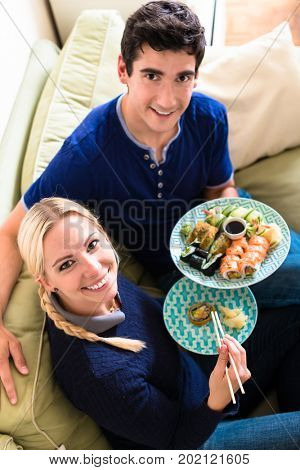High angle view portrait of happy young couple looking at camera while eating traditional Asian food at home