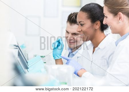 Group of researchers during work on devices in laboratory doing experiment