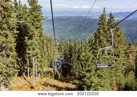 Family in chair lift going up mountain for a hike
