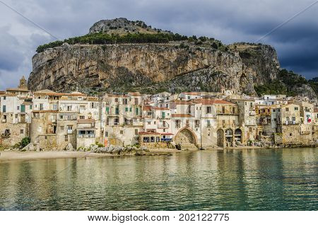 Beach of cefalu with its old constructions and in the background a great formation known as the rock on the same are the ruins of the ancient temple of diana