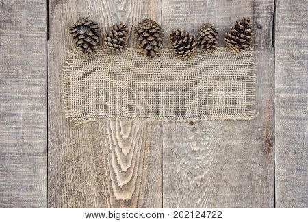 Country Burlap With Pinecones Along Top Border On Rustic Wood Background