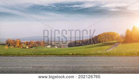 Autumn rural road with beautiful landscape behind it.